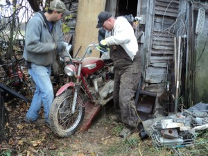 Scott and Nav pulling a motorcycle from a chicken coop